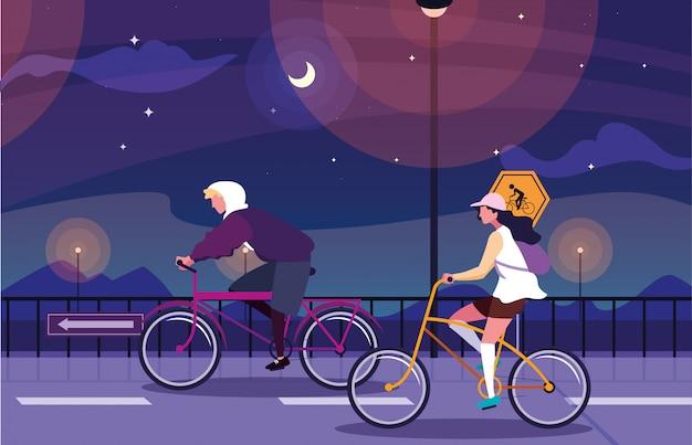 Coppia in sella a bici nel paesaggio notturno con segnaletica per ciclista