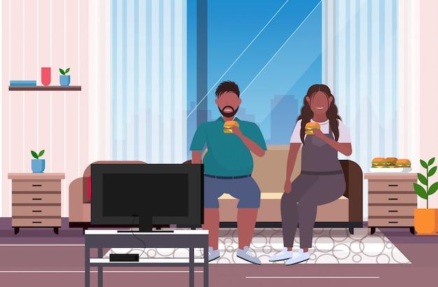 Coppia mangiare hamburger fast food sovrappeso uomo donna guardando la tv seduto sul divano malsano nutrizione obesità concetto soggiorno interno a figura intera orizzontale