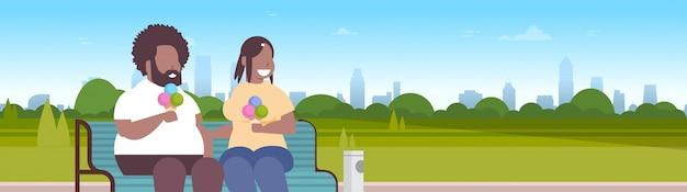 Coppia seduta panchina in legno a mangiare il gelato uomo donna divertirsi rilassante nel parco cittadino al tramonto