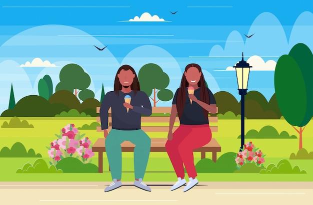 Coppia seduta su una panchina in legno a mangiare il gelato in sovrappeso uomo donna divertirsi malsano nutrizione obesità concetto estate parco paesaggio a figura intera orizzontale