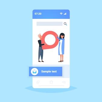 Coppia utilizzando l'app di navigazione online geo pin tag pointer uomo donna holding indicatore posizione gps concetto smartphone schermo applicazione mobile integrale