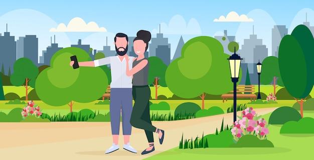 Coppie della donna dell'uomo che prendono la foto del selfie sulla macchina fotografica dello smartphone personaggi dei cartoni animati femminili maschii che abbracciano orizzontale integrale del fondo di paesaggio urbano del parco urbano della città all'aperto