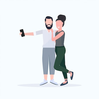 Coppie della donna dell'uomo che prendono la foto del selfie sulla macchina fotografica dello smartphone personaggi dei cartoni animati femminili maschii che abbracciano posa sul fondo bianco integrale