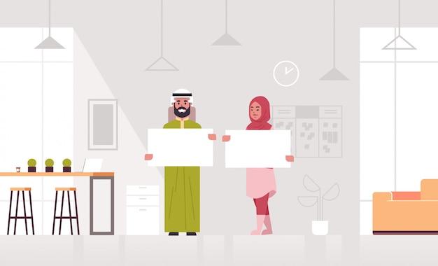 Coppie delle persone di affari che tengono i soci arabi vuoti vuoti della donna dell'uomo di affari dell'insegna in bianco che mostrano orizzontale bianco integrale interno di concetto moderno della pubblicità del cartone bianco