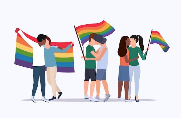 Coppie dello stesso sesso tenendo arcobaleno bandiera mix gara lesbiche gay baciare amore parata lgbt orgoglio festival concetto personaggi dei cartoni animati in piedi insieme a figura intera piatta orizzontale