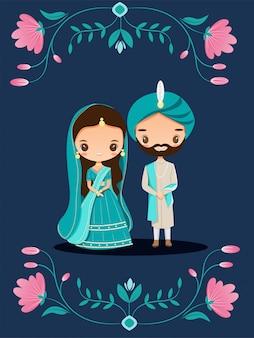 Coppie indiane sveglie in vestito tradizionale sulla partecipazione di nozze floreale