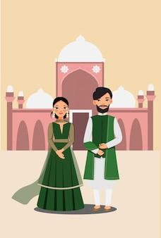 Coppie sveglie in vestito tradizionale con il vettore buiding masjid famoso di pakistand