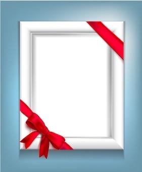 Cornice bianca realistica con un nastro rosso legato agli angoli con un fiocco rosso su sfondo blu. illustrazione
