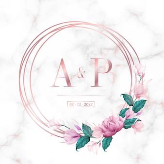 Cornice circolare in oro rosa con motivi floreali su fondo in marmo per logo monogramma di nozze e carta di invito