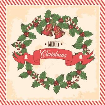 Corona di natale vintage di foglie di agrifoglio, campane e caramelle con scritta saluto sulla cartolina d'auguri nera