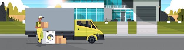 Corriere vicino camion di consegna con scatole di cartone lavatrice elettrodomestici negozio di acquisto delle merci concetto di distribuzione casa cottage esterno a figura intera orizzontale