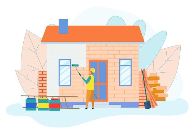 Costruttore operaio che vernicia la parete della casa del piano unico