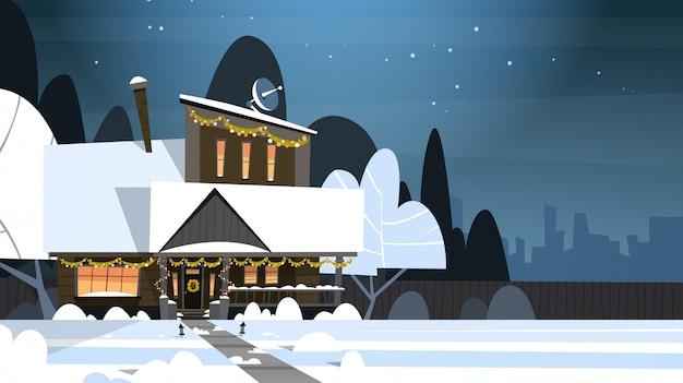 Costruzione della casa del paesaggio di inverno del villaggio con neve sulla via principale del sobborgo della città o della città alla notte