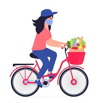 Covid19. epidemia di coronavirus. consegna sicura degli alimenti. la ragazza del corriere in una maschera protettiva consegna cibo in bicicletta