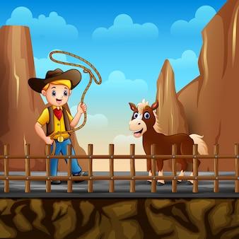 Cowboy e un cavallo nel paesaggio desertico