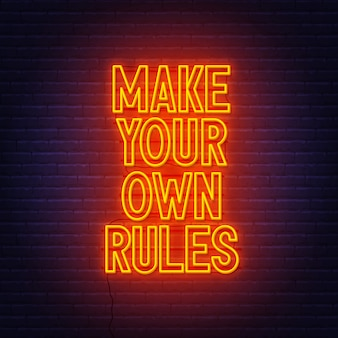 Crea le tue regole insegna al neon sul muro di mattoni.