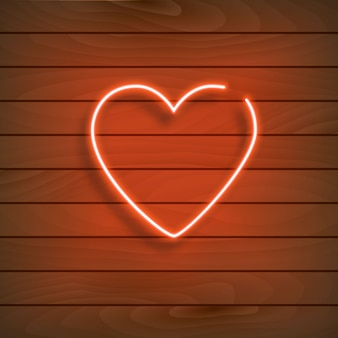 Cuore al neon un segno rosso brillante su una parete di legno.