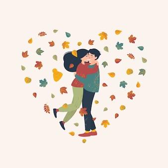 Cuore di foglie autunnali contro cui spicca una coppia innamorata