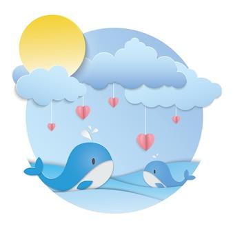 Cuore rosa appeso e due balene blu nell'oceano