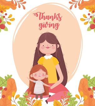 Decorazione felice del fogliame di caduta di seduta della madre e della figlia di giorno felice di ringraziamento