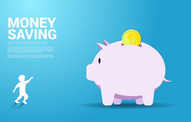 Dito del punto del bambino in avanti al grande porcellino salvadanaio con moneta