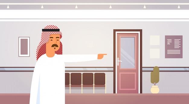 Dito di punto arabo dell'uomo di affari sull'imprenditore delle porte in ufficio moderno