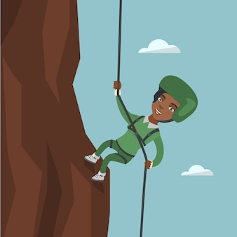 Donna africana che arrampica una montagna con la corda.
