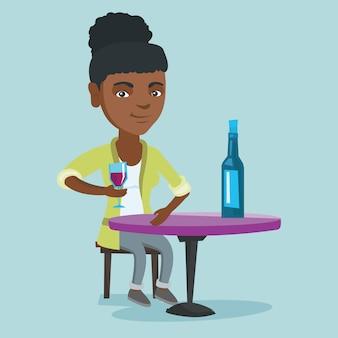 Donna africana che beve vino nel ristorante.