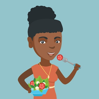 Donna africana che mangia insalata di verdure sana.