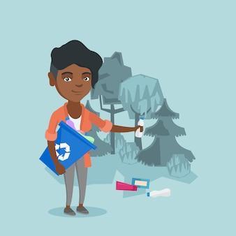 Donna africana che raccoglie immondizia nella foresta.