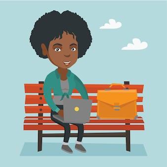 Donna africana di affari che lavora al computer portatile all'aperto.