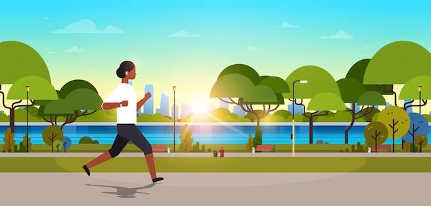 Donna afro-americana jogging all'aperto moderno parco pubblico