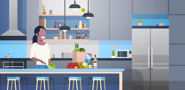 Donna afroamericana che cucina insalata nella stanza moderna della cucina