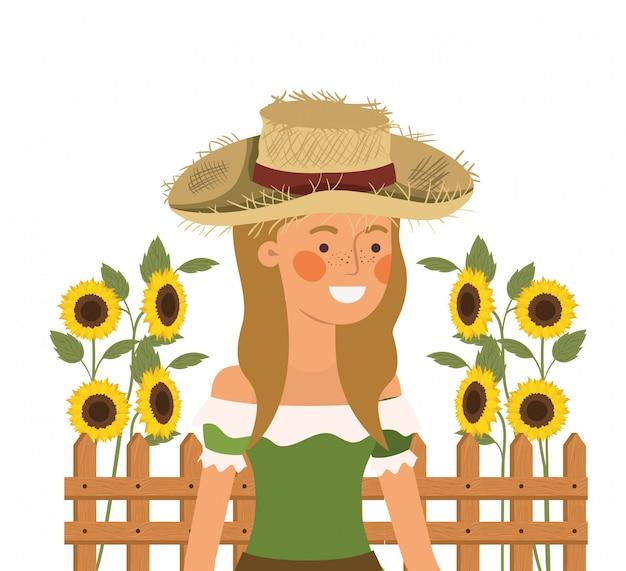 Donna agricoltore con cappello di paglia e girasoli