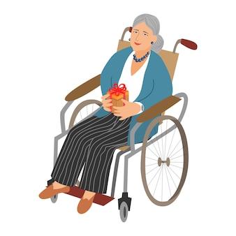 Donna anziana in sedia a rotelle con un regalo in mano.