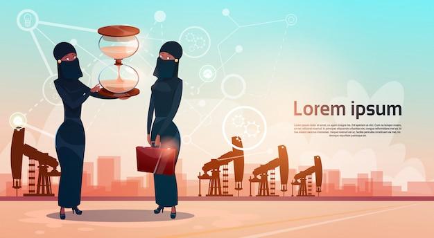 Donna araba con il concetto di ricchezza della piattaforma della gru dell'impianto di perforazione di petrolio di pumpjack dei soldi dell'orologio della sabbia