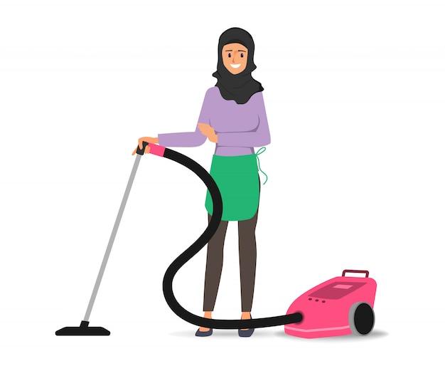 Donna araba musulmana che usando l'aspirapolvere sul carattere del pavimento.