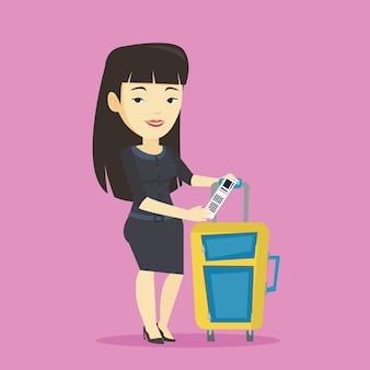 Donna asiatica di affari che mostra l'etichetta dei bagagli.