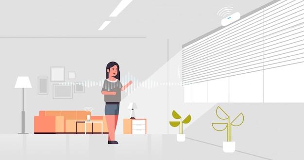 Donna casual utilizzando l'assistente digitale attivato per il riconoscimento vocale dell'altoparlante intelligente