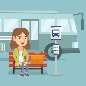 Donna caucasica che aspetta un bus alla fermata dell'autobus.