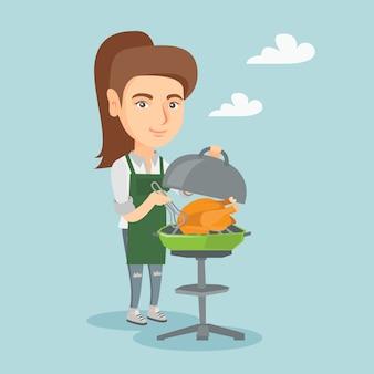 Donna caucasica che cucina pollo sul barbecue.