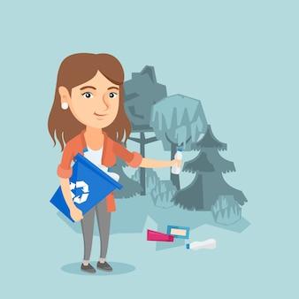 Donna caucasica che raccoglie immondizia nella foresta.