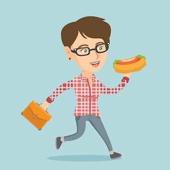 Donna caucasica di affari che mangia hot dog in fuga
