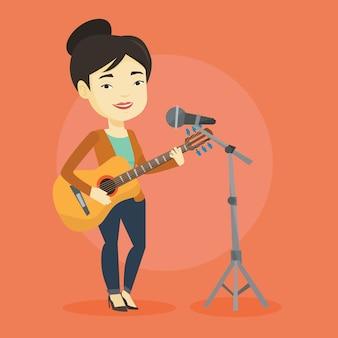 Donna che canta nel microfono e suonare la chitarra.