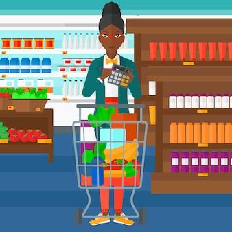 Donna che conta sul calcolatore nel supermercato