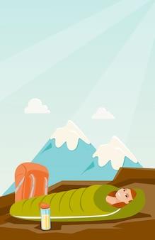 Donna che dorme in un sacco a pelo in montagna.