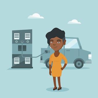 Donna che fa pagare automobile elettrica alla stazione di carico.