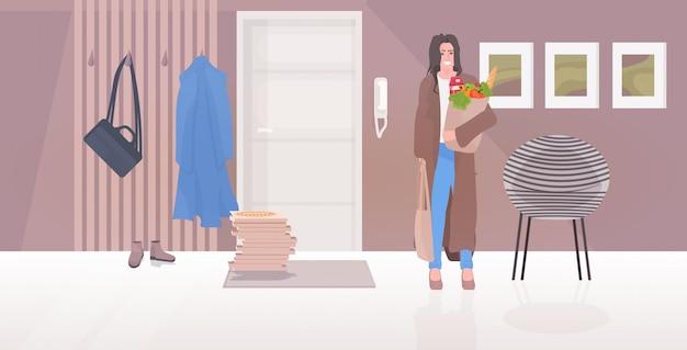 Donna che giudica il sacco di carta della drogheria in pieno di alimento fresco e del concetto di lavoretti di compera dei prodotti quotidiani