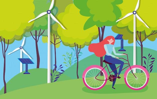 Donna che guida una bici vicino ai generatori eolici