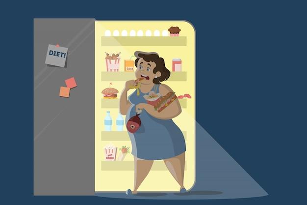 Donna che mangia di notte vicino al frigorifero.